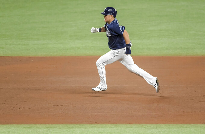 Tampa Bay Rays' Yoshi Tsutsugo races toward third base on a double hit by Francisco Mejia during the fourth inning of a baseball game against the Oakland Athletics Tuesday, April 27, 2021, in St. Petersburg, Fla. (AP Photo/Steve Nesius)
