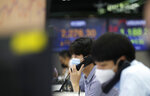 A currency trader talks on the phone at the foreign exchange dealing room in Seoul, South Korea, Thursday, July 30, 2020. Asian stocks advanced Thursday after the U.S. Federal Reserve left interest rates near zero to support a struggling economy.(AP Photo/Lee Jin-man)