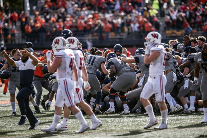 Wisconsin players walk off the field as Illinois celebrates their 24-21 win in an NCAA college football game, Saturday, Oct.19, 2019, in Champaign, Ill. (AP Photo/Holly Hart)