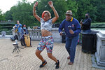 In this Tuesday, June 16, 2020, photo, a woman dances to the music as Alix Julien, right, augments the beat with maracas during a free concert by Alegba and Friends at Brooklyn's Prospect Park boathouse in New York. Before the pandemic, the band had weekly gigs in local bars and restaurants. But since coronavirus, without a music venue to play in, the group has taken their music to the park, where they've developed a devoted following of regular listeners while attracting a larger fan base. (AP Photo/Kathy Willens)