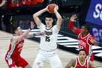 Purdue center Zach Edey (15) looks to pass between Ohio State forward Kyle Young (25) and forward E.J. Liddell (32) in the first half of an NCAA college basketball game at the Big Ten Conference tournament in Indianapolis, Friday, March 12, 2021. (AP Photo/Michael Conroy)