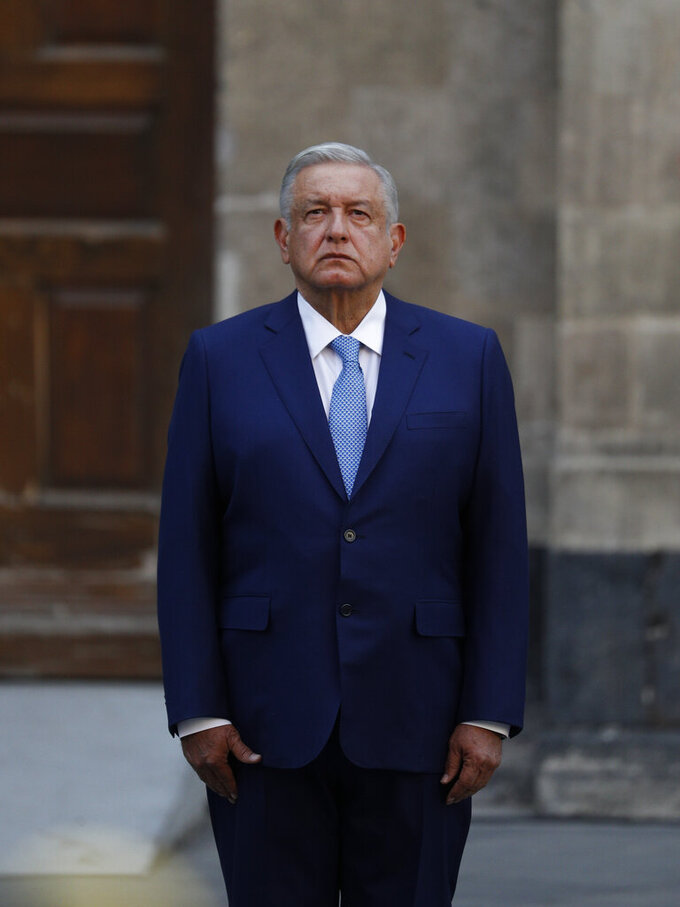 Mexican President Andres Manuel Lopez Obrador stands at attention during a ceremony before a news conference marking the 100th day of his third year in office, at the National Palace in Mexico City, Tuesday, March 30, 2021. (AP Photo/Eduardo Verdugo)