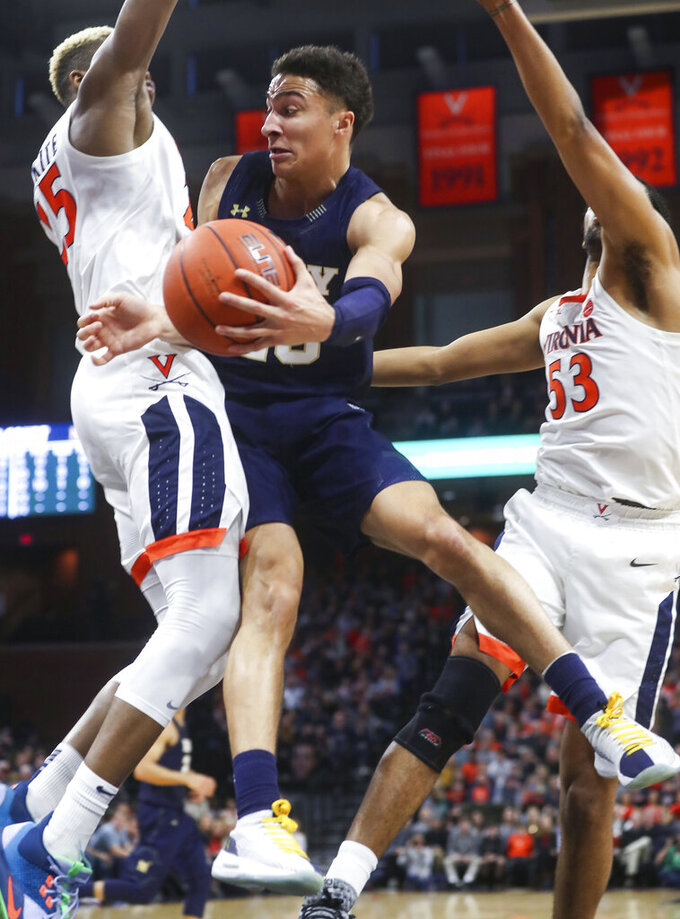 Navy guard Greg Summers (20) passes the ball next to Virginia forward Mamadi Diakite (25) and guard Tomas Woldetensae (53) during an NCAA college basketball game in Charlottesville, Va., Sunday, Dec. 29, 2019. (AP Photo/Andrew Shurtleff)