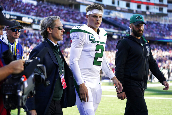 New York Jets quarterback Zach Wilson (2) is escorted to the locker room after an apparent injury during the first half of an NFL football game against the New England Patriots, Sunday, Oct. 24, 2021, in Foxborough, Mass. (AP Photo/Steven Senne)