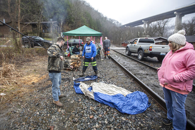 In this Tuesday, Jan. 14, 2020, photo, miners, who say they haven't been paid in nearly three weeks, set up a tent at the site where they block a coal train in the Kimper area of Pike County, Ky. A group of Kentucky coal miners who blocked a railroad track for three days over unpaid wages have ended their protest, claiming victory with their paychecks.  (Ryan C. Hermens/Lexington Herald-Leader via AP)