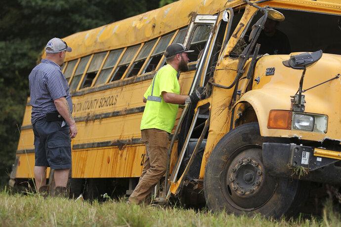 Wrecker crews inspect the damage to a Benton County School bus that was involved in wreck along U.S. Highway 72 near Walnut, Miss., Tuesday, Sept. 10, 2019, that resulted in the death of the driver and sent several students to the hospital. (Thomas Wells/The Northeast Mississippi Daily Journal via AP)