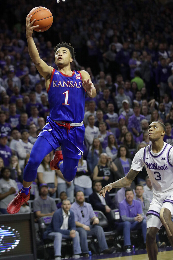 Kansas guard Devon Dotson (1) makes a basket in front of Kansas State guard DaJuan Gordon (3) during the first half of an NCAA college basketball game in Manhattan, Kan., Saturday, Feb. 29, 2020. (AP Photo/Orlin Wagner)