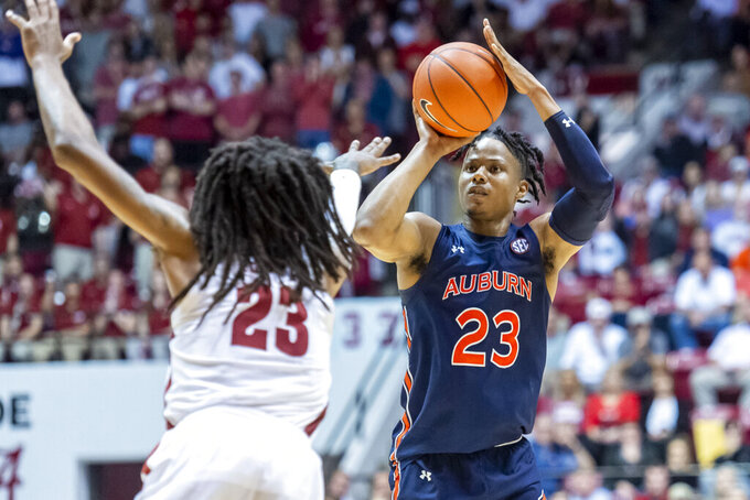 Auburn forward Isaac Okoro (23) shoots a three as Alabama guard John Petty Jr. (23) arrives late to defend the shot during the first half of an NCAA college basketball game, Wednesday, Jan. 15, 2020, in Tuscaloosa, Ala. (AP Photo/Vasha Hunt)