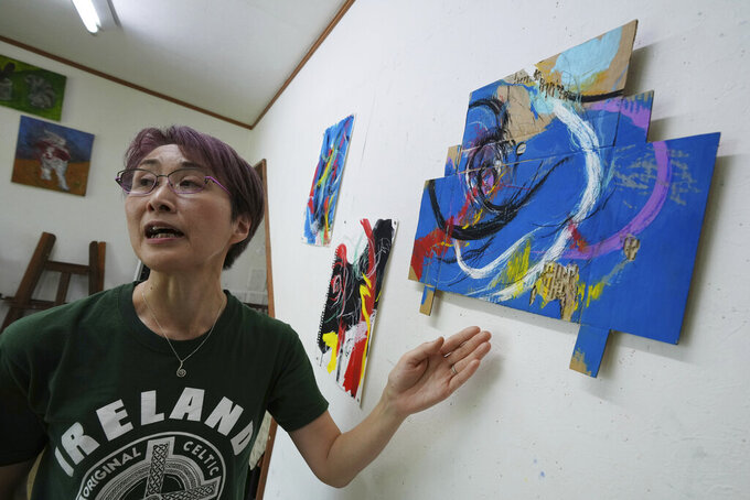 """Japanese artist Miwako Sakauchi speaks about her art work for Art Exhibition """"Declaration of the end of Olympic games"""" in Chiba near Tokyo, Thursday, June 10, 2021. Polls have found an overwhelming majority of Japanese people are skeptical of the Tokyo Olympics being held this summer during a pandemic, but only a few have publicly marched to protest. But there are creative projects that are looking to protest the increasingly unpopular Tokyo Olympics, even as authorities seek to shut them down.(AP Photo/Eugene Hoshiko)"""