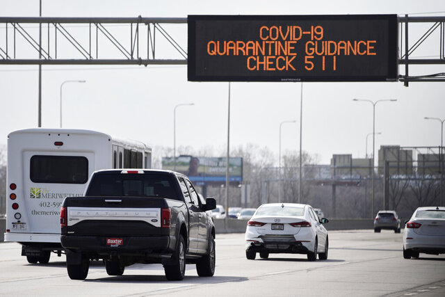 A road sign over Interstate 80 in Omaha, Neb., directs motorists to contact 511 for Covid-19 quarantine guidance, Tuesday, March 31, 2020. Travelers coming back to Nebraska from out of state are advised to self-quarantine for 14 days. This includes snowbirds returning to Nebraska after having spent the winter in places like Arizona, Florida, or Texas, or those visiting secondary residences within Nebraska. However, the guidance to self-quarantine does not apply to commuters or workers in the transportation industry. (AP Photo/Nati Harnik)