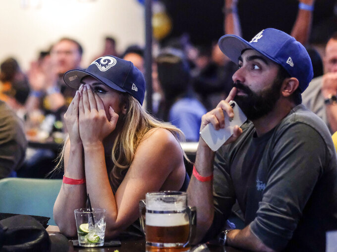 Ella Silver, left, and Moe Helmy react during a viewing party for the Super Bowl 53 football game between the New England Patriots and the Los Angeles Rams in Los Angeles, Sunday, Feb. 3, 2019. (AP Photo/Ringo H.W. Chiu)
