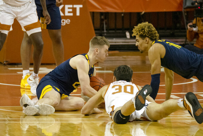 West Virginia guard Sean McNeil, left, and forward Emmitt Matthews, Jr., right, fight for a loose with Texas forward Brock Cunningham (30) during the second half of an NCAA college basketball game, Saturday, Feb. 20, 2021, in Austin, Texas. McNeil recovered the ball and Cunningham was call for a foul. West Virginia won 84-82. (AP Photo/Michael Thomas)