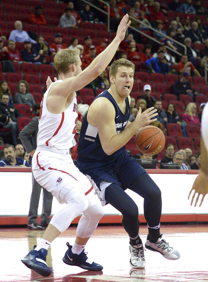 Utah State's Quinn Taylor, right, drives around Fresno State's Sam Bittner during an NCAA college basketball game in Fresno, Calif., Tuesday, Feb. 5, 2019. (Craig Kohlruss/The Fresno Bee via AP)