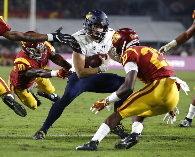 California quarterback Chase Garbers, center, eludes both Southern California linebacker John Houston Jr., left, and cornerback Ajene Harris, right, to score during the second half of an NCAA college football game in Los Angeles, Saturday, Nov. 10, 2018. California won 15-14. (AP Photo/Alex Gallardo)