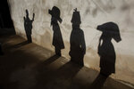Shadows of revelers of the Estrela Dalva Folia de Reis Group are cast on a wall as they perform during Epiphany, or Three Kings Day celebration in the city of Planaltina, Brasilia, Brazil, Monday, Jan. 6, 2020. Folia de Reis is a Brazilian procession that depicts the Biblical journey of the Three Kings, Gaspar, Melchior, and Balthazar, to visit the Christ Child. (AP Photo/Eraldo Peres)