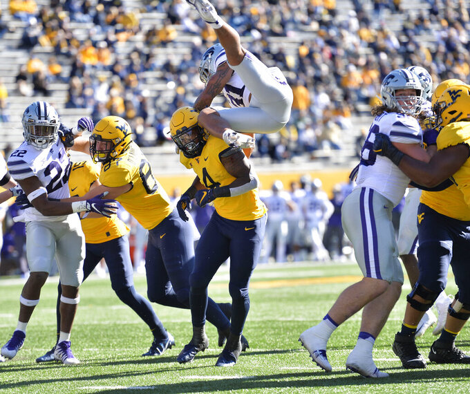 Kansas State defensive back Jahron McPherson (31) leaps over West Virginia  running back Leddie Brown (4) as he attempts to block a pass during an NCAA college football game Saturday, Oct. 31, 2020, in Morgantown, W.Va. (William Wotring/The Dominion-Post via AP)