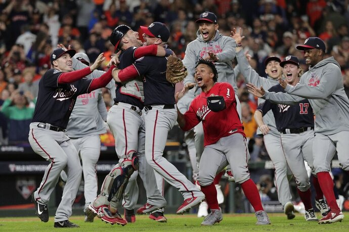 FILE - In this Oct. 30, 2019, file photo, Washington Nationals' Yan Gomes and Daniel Hudson celebrate after Game 7 of the baseball World Series against the Houston Astros, in Houston. A full postseason share on World Series champion Washington was worth $382,358, down from $416,838 for Boston last year and a record $438,902 for Houston in 2017. The commissioner's office said Tuesday, Nov. 26, 2019, that the Nationals voted 61 full shares, 14.13 partial shares and two cash awards. The Red Sox had 66 full shares, 10.025 partial shares and eight cash awards. The players' pool was $80.86 million, the third-highest behind a record $88.19 million last year and $84.5 million in 2017. (AP Photo/David J. Phillip, File)