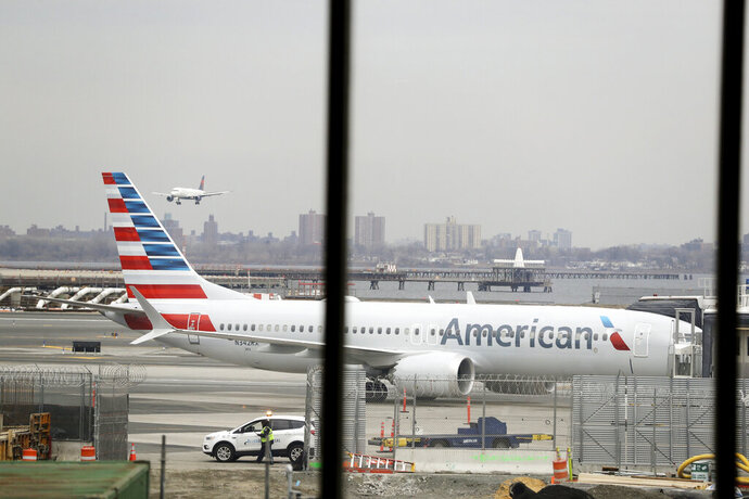 FILE - In a March 13, 2019 file photo, an American Airlines Boeing 737 MAX 8 sits at a boarding gate at LaGuardia Airport in New York. American Airlines is canceling 115 flights per day through mid-August because of ongoing problems with the Boeing 737 Max aircraft. (AP Photo/Frank Franklin II, File)