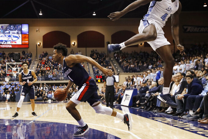 Gonzaga guard Admon Gilder drives toward the basket past a leaping San Diego guard Sabry Philip (4) during the first half of an NCAA college basketball game Thursday, Jan. 9, 2020, in San Diego. (AP Photo/Gregory Bull)