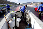 """A crew readies the track at Bandimere Speedway west of Denver on May 5, 2021. The Colorado State Patrol runs a program called """"Take it to the Track"""" in hopes of luring racers away from public areas to a safer and more controlled environment, even allowing participants to race a trooper driving a patrol car. The program's goals have gained new importance and urgency this year as illegal street racing has increased amid the coronavirus pandemic. (AP Photo/Thomas Peipert)"""