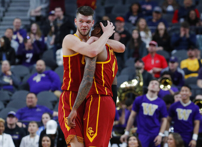 Southern California's Kevin Porter Jr., right, and Nick Rakocevic celebrate after a play against Washington during the first half of an NCAA college basketball game in the quarterfinal round of the Pac-12 conference tournament Thursday, March 14, 2019, in Las Vegas. (AP Photo/John Locher)