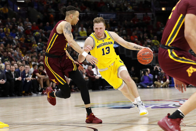 Michigan's Ignas Brazdeikis (13) drives against Minnesota's Amir Coffey (5) during the second half of an NCAA college basketball game in the semifinals of the Big Ten Conference tournament, Saturday, March 16, 2019, in Chicago. (AP Photo/Nam Y. Huh)