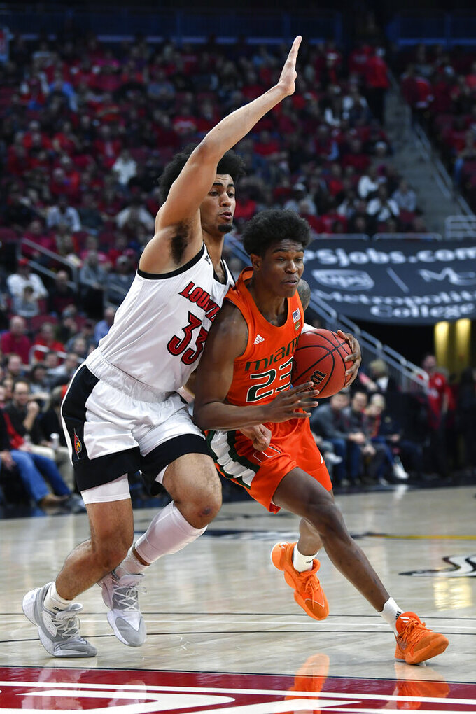 Miami guard Kameron McGusty (23) is defended by Louisville forward Jordan Nwora (33) during the first half of an NCAA college basketball game in Louisville, Ky., Tuesday, Jan. 7, 2020. (AP Photo/Timothy D. Easley)