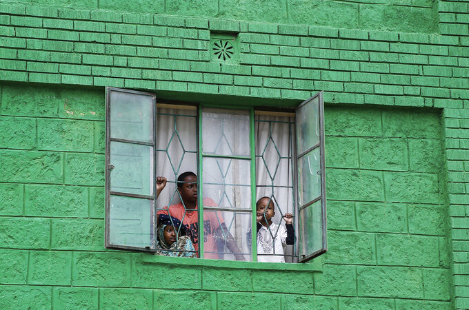 """Youths in an apartment look out of their window as residents below protest on the streets, asking the government to supply them with food and to be allowed to leave, in the Eastleigh area of Nairobi, Kenya, on Monday, May 11, 2020. A week earlier, the Kenyan government sealed off Eastleigh and the Old Town area of the port city of Mombasa, with no movement permitted in or out for 15 days, due to """"a surge in the number of positive coronavirus cases."""" (AP Photo/Brian Inganga)"""