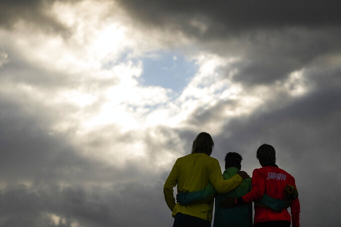 Brazil's Italo Ferreira, center, gold medal, Japan's Kanoa Igarashi, right, silver medal, and Australia's Owen Wright, bronze medal, pose for photographers in the men's surfing competition at the 2020 Summer Olympics, Tuesday, July 27, 2021, at Tsurigasaki beach in Ichinomiya, Japan. (AP Photo/Francisco Seco)