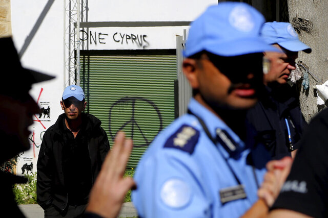 United Nations peacekeepers stand inside the UN buffer zone during a protest from Greek and Turkish Cypriots against a closed crossing point in the ethnically divided capital Nicosia, Cyprus, Saturday, March 7, 2020. Demonstrators staged another protest against a decision by the Cyprus government to temporarily shut four of nine crossing points along a United Nations controlled buffer zone that separates the south from the breakaway Turkish Cypriot north. The Cypriot government says it shut the crossing points to better check for potential coronavirus carriers at the other crossing points. (AP Photo/Petros Karadjias)