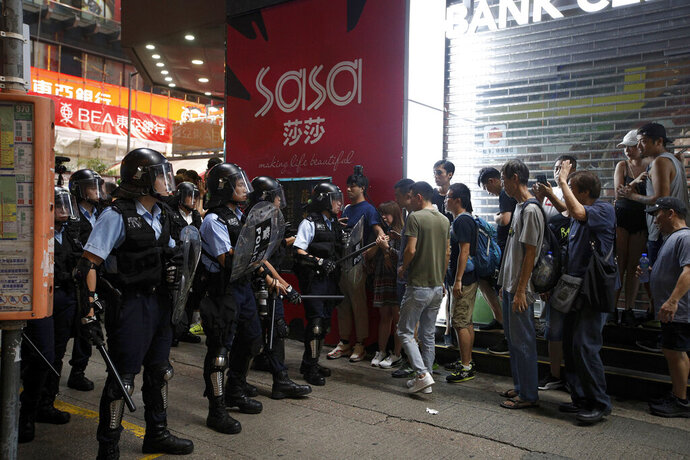 In this July 7, 2019, photo, riot police prevent people, some are mainland Chinese tourists, from crossing a street during a face-off with protesters at the Mongkok, a popular place with mainland Chinese tourists in Hong Kong. It's still the world's