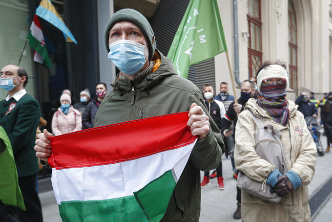 A man holds a Hungarian flag during a protest in Budapest, Hungary, Monday, March 15, 2021. Hungarians gathered on the country's national day to protest against the current lockdown measures after new restrictive measures were introduced by the Hungarian government last week aiming to slow a record-breaking wave of COVID-19 hospitalizations and deaths. (AP Photo/Laszlo Balogh)