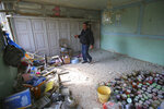 A local resident walks in an apartment building that was allegedly damaged by recent shelling during fighting over the breakaway region of Nagorno-Karabakh in Tartar region, Azerbaijan, Wednesday, Sept. 30, 2020. Leaders of Azerbaijan and Armenia brushed off the suggestion of peace talks Tuesday, accusing each other of obstructing negotiations over the separatist territory of Nagorno-Karabakh, with dozens killed and injured in three days of heavy fighting. (AP Photo/Aziz Karimov)