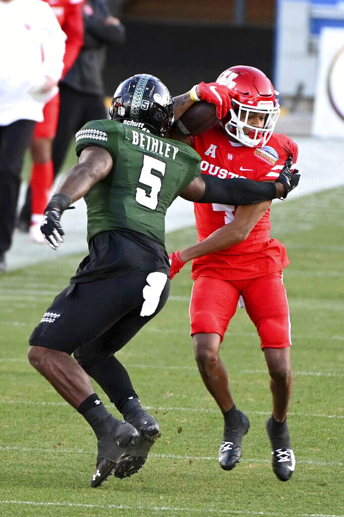 Houston wide receiver Nathaniel Dell (4) looks for running room around Hawaii defensive back Khoury Bethley (5) in the third quarter of the New Mexico Bowl NCAA college football game in Frisco, Texas, Thursday, Dec. 24, 2020. (AP Photo/Matt Strasen)