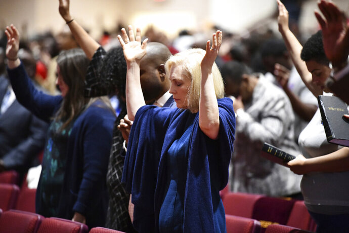 FILE - In this Feb. 10, 2019, file photo, Sen. Kirsten Gillibrand, D-N.Y., worships at Mount Moriah Missionary Baptist Church in North Charleston, S.C. By now, most Democratic presidential candidates have polished their stump speeches. But when they're in South Carolina, they may need to add in a sermon. In a large and diverse primary field, White House hopefuls are angling to develop relationships with black churches. (AP Photo/Meg Kinnard, File)