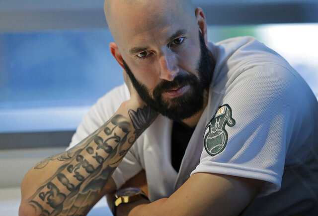 FILE - In this Jan. 24, 2020, file photo, Oakland Athletics pitcher Mike Fiers ponders a question during an interview with the media in Oakland, Calif. The Associated Press looks at some of the events that would have been live the week of April 20-26: _ Sign-stealing whistleblower Mike Fiers would have been in Houston with the Oakland A's for a weekend series. The A's right-hander, who pitched for the 2017 World Series champion Astros, hasn't been back to Minute Maid Park since saying last November that his former team used a camera in center field to steal signs. (AP Photo/Ben Margot, File)