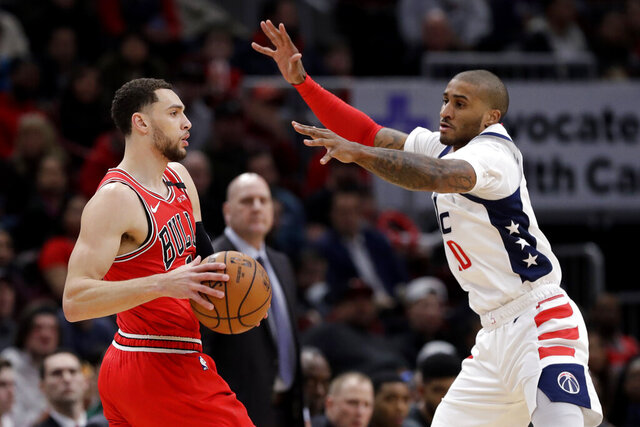 Chicago Bulls guard Zach LaVine, left, looks to pass the ball as Washington Wizards guard Gary Payton II defneds during the first half of an NBA basketball game in Chicago, Wednesday, Jan. 15, 2020. (AP Photo/Nam Y. Huh)
