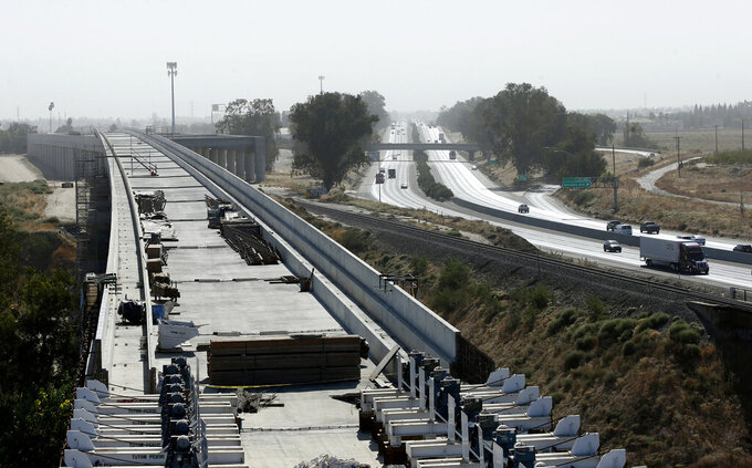 """FILE - This Oct. 9, 2019, file photo, shows the high-speed rail viaduct paralleling Highway 99 near Fresno, Calif. California Gov. Gavin Newsom on Friday, May 14, 2021, proposed spending $11 billion on transportation improvements, half of it for a troubled bullet train intended to eventually link California's major metropolitan areas and for projects supporting the 2028 Summer Olympics in Los Angeles. High-Speed Rail Authority spokeswoman Melissa Figueroa said Newsom """"expressed the optimism we all share"""" that the federal government will now provide $929 million withdrawn by Trump's administration. (AP Photo/Rich Pedroncelli, File)"""