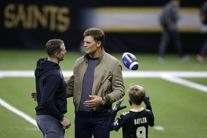 New Orleans Saints quarterback Drew Brees, left, speaks with Tampa Bay Buccaneers quarterback Tom Brady as Bree's children look on after an NFL divisional round playoff football game between the New Orleans Saints and the Tampa Bay Buccaneers, Sunday, Jan. 17, 2021, in New Orleans. The Tampa Bay Buccaneers won 30-20. (AP Photo/Butch Dill)