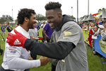 NFC linebacker Shaquil Barrett, of the Tampa Bay Buccaneers,, right, shakes hands with quarterback Russell Wilson, of the Seattle Seahawks, after a practice for the NFL Pro Bowl football game Thursday, Jan. 23, 2020, in Kissimmee, Fla. (AP Photo/Chris O'Meara)