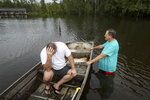 Stephen Gilbert, left, and his father-in-law sit in front of their flooded property on Friday, Sept. 20, 2019, in the Mauriceville, Texas, area. Floodwaters are starting to recede in most of the Houston area after the remnants of Tropical Storm Imelda flooded parts of Texas.