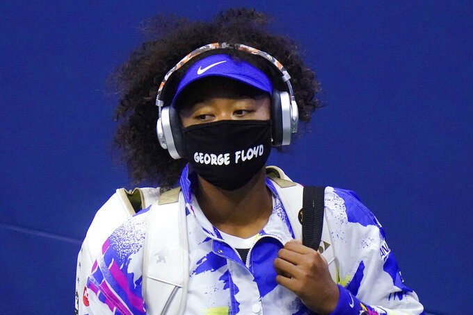 """Naomi Osaka, of Japan, wears a protective mask due to the COVID-19 virus outbreak, featuring the name """"George Floyd"""", while arriving on court to face Shelby Rogers, of the United States, during the quarterfinal round of the US Open tennis championships, Tuesday, Sept. 8, 2020, in New York. (AP Photo/Frank Franklin II)"""