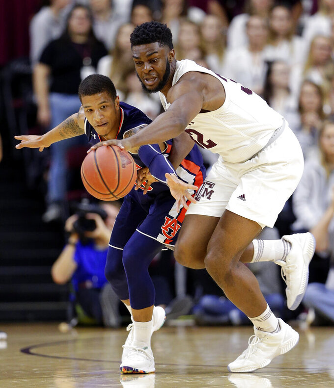 Auburn guard Samir Doughty, left, loses a loose ball scramble to Texas A&M forward Josh Nebo during the first half of an NCAA college basketball game, Wednesday, Jan. 16, 2019, in College Station, Texas. (AP Photo/Michael Wyke)