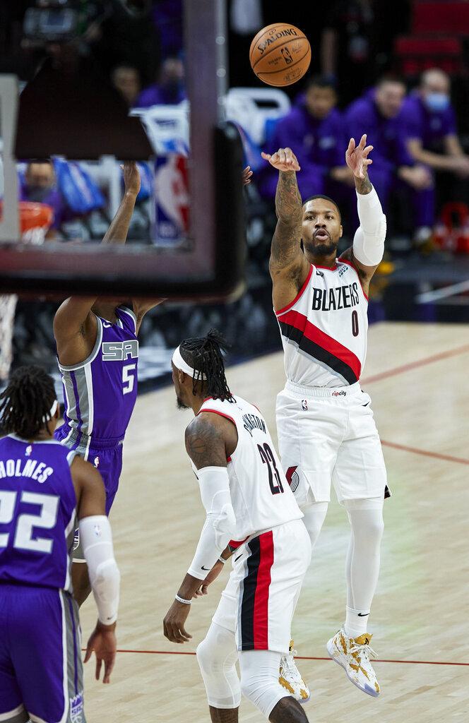 Portland Trail Blazers guard Damian Lillard shoots next to Sacramento Kings guard De'Aaron Fox during the first half of a preseason NBA basketball game in Portland, Ore., Friday, Dec. 11, 2020. (AP Photo/Craig Mitchelldyer)