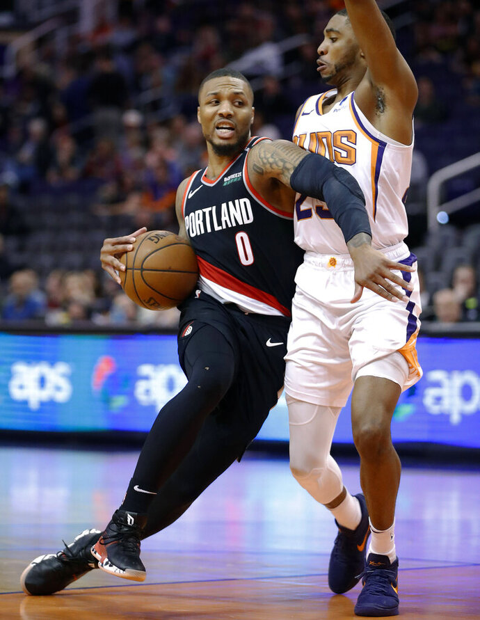 Portland Trail Blazers guard Damian Lillard (0) drives around Phoenix Suns forward Mikal Bridges during the second half of an NBA basketball game Thursday, Jan. 24, 2019, in Phoenix. (AP Photo/Matt York)