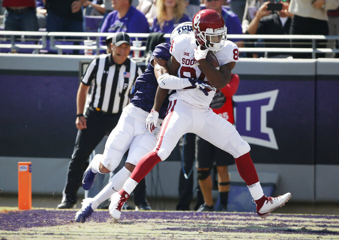 Oklahoma wide receiver Lee Morris (84) scores a touchdown as TCU safety Trevon Moehrig-Woodard (17) defends during the second half of an NCAA college football game, Saturday, Oct. 20, 2018, in Fort Worth, Texas. Oklahoma won 52-27. (AP Photo/Brandon Wade)