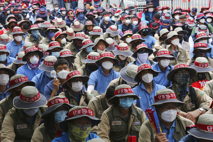 Workers wearing face masks to help protect against the spread of the new coronavirus stage a rally against the government's labor policy in Seoul, South Korea, Wednesday, June 10, 2020. The letters head bands read
