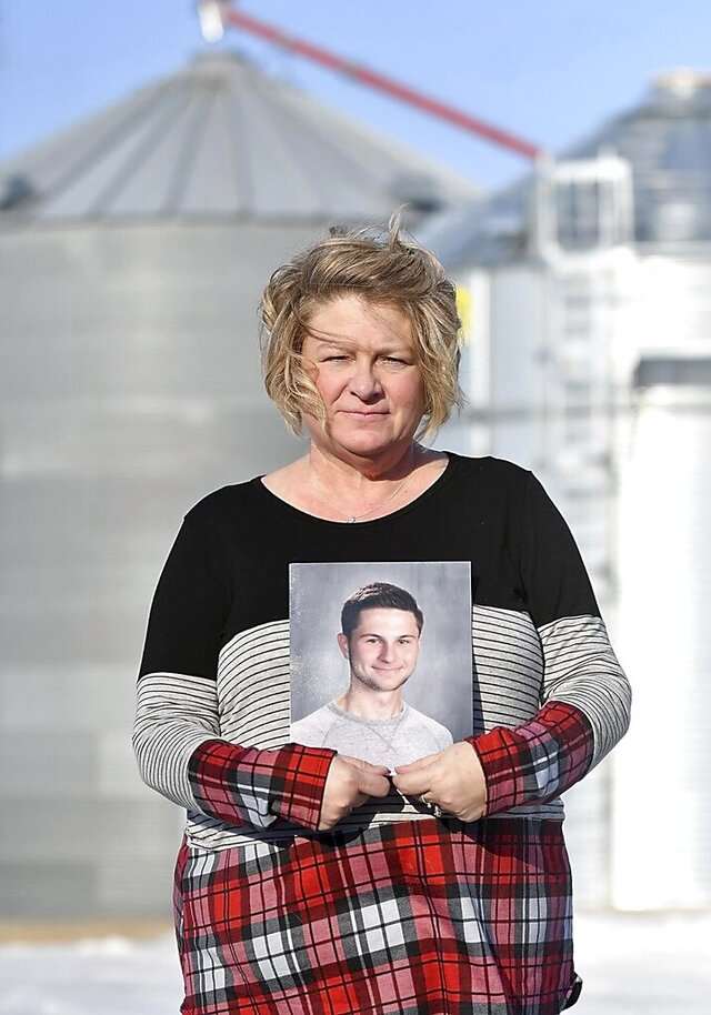 Michele Gran, shown here holding a photo of her 18-year-old son, Landon on her family's farm near Norseland, Minn., plans to advocate for more safety features in and around grain bins this legislative session after  Landon, died in August inside a grain bin two miles south of his home in Norseland. Landon is one of at least nine people who died in grain bin-related incidents since July. (Pat Christman/The Free Press via AP)