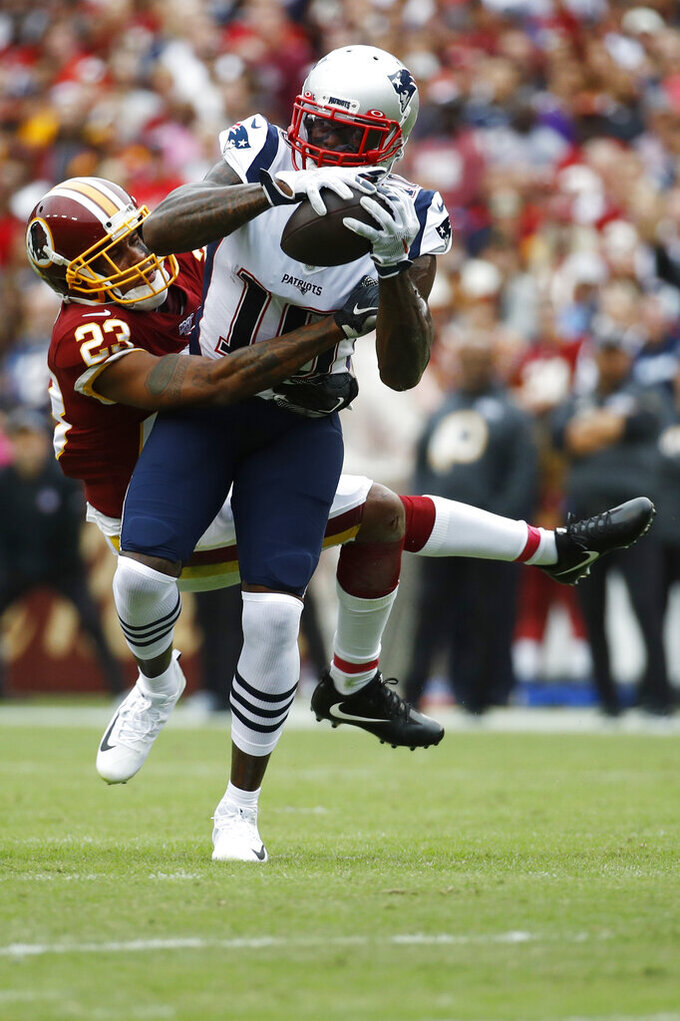 New England Patriots wide receiver Josh Gordon (10) makes the catch against Washington Redskins cornerback Quinton Dunbar (23) during the first half of an NFL football game, Sunday, Oct. 6, 2019, in Washington. (AP Photo/Patrick Semansky)