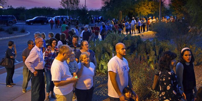 FILE - In this March 22, 2016, file photo, people wait in line to vote in a primary election in Chandler, Ariz. A group of independents is making a longshot push to convince the Arizona Democratic Party to open its presidential primary to voters who decline to join a political party. Party activists are expected to debate the issue at a meeting in Prescott on Saturday, Sept. 21, 2019. (David Kadlubowski/The Arizona Republic via AP, File)
